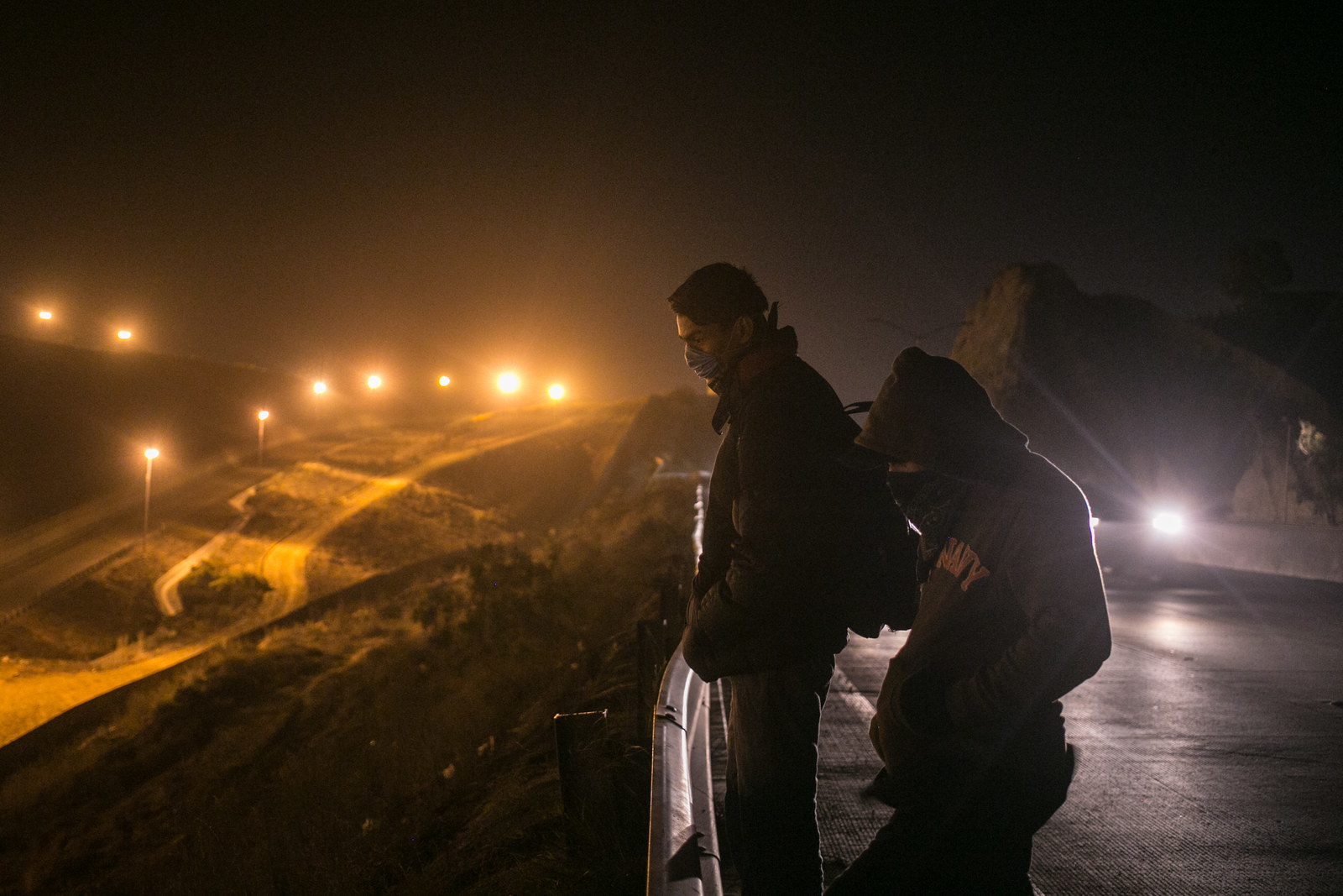 Two members of the caravan, who declined to give their names, look at the border wall from the highway in Tijuana, Dec. 1.