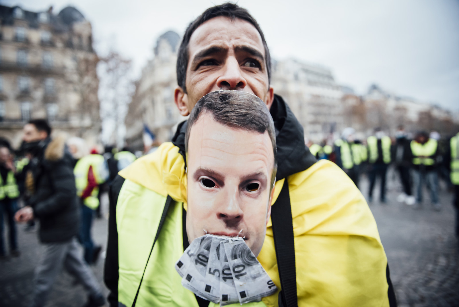 A man wears a mask of French President Emmanuel Macron during the Yellow Vest demonstration on Dec. 8, 2018.