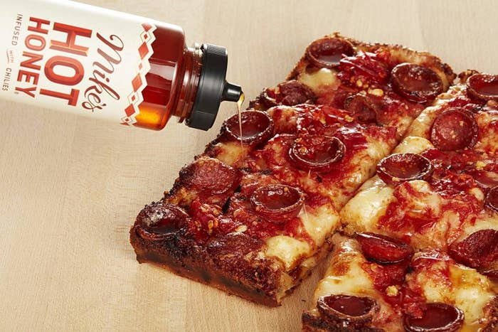 The bottle of honey honey pouring onto a pepperoni pizza