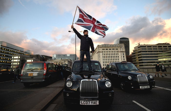 London, January 18 A black cab driver waves a union flag while standing on a taxi on London Bridge, during a protest against Transport for London and Uber.