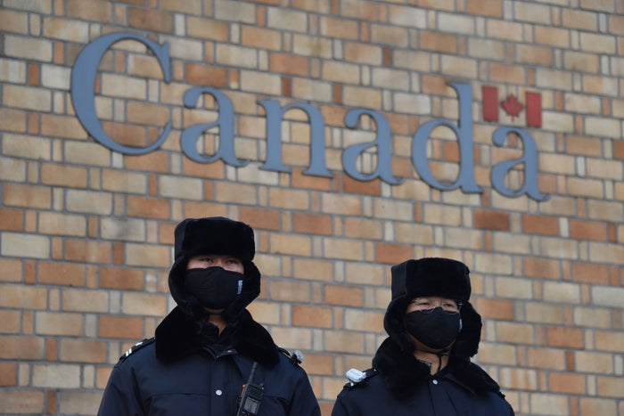 Chinese police officers stand guard outside the Canadian embassy in Beijing.