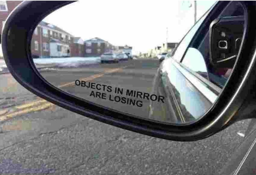 "A photo of a side view mirror with the sticker that reads, ""Objects in mirror are losing."""