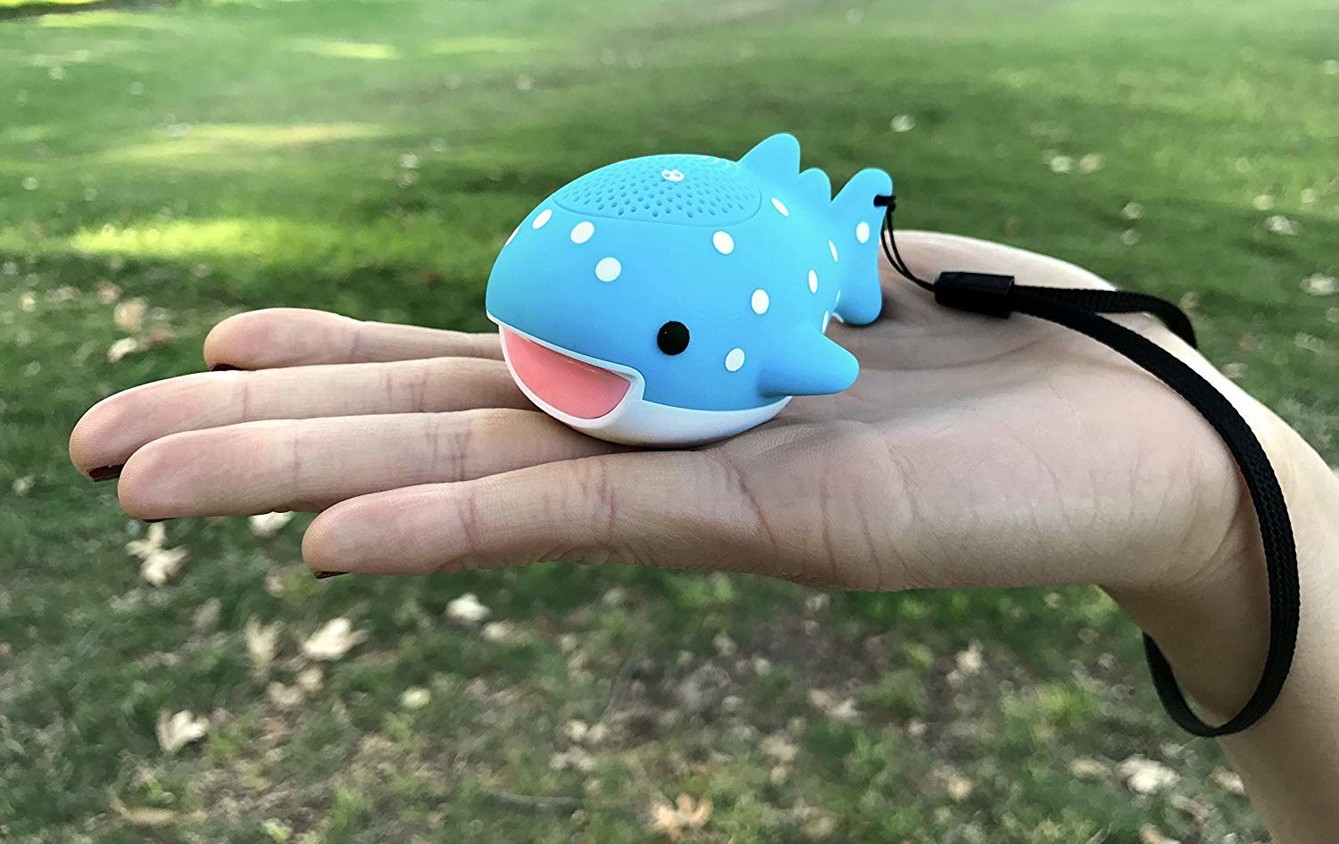 A hand holding the small whale-shaped speaker with a wrist loop
