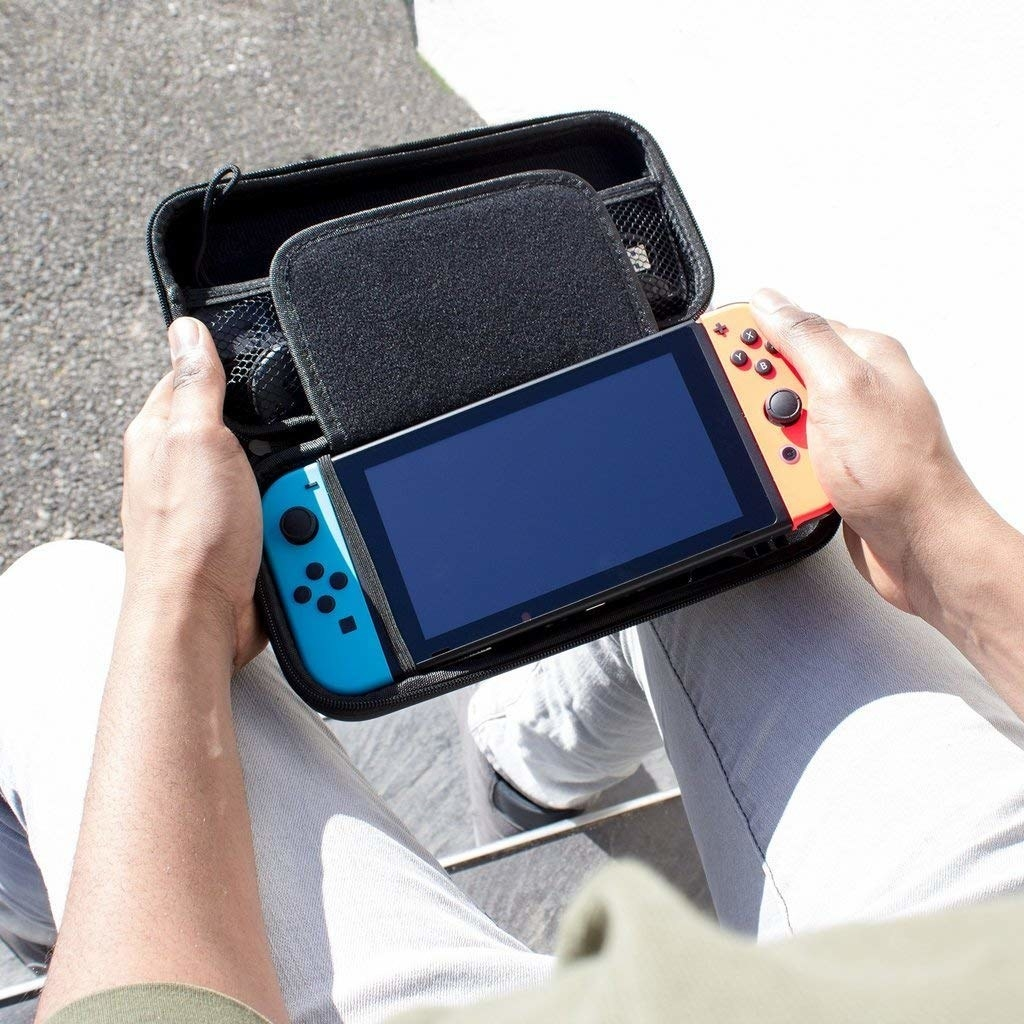 a model taking their switch out of the simple black carrying case