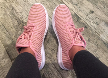 A customer review photo of a person wearing the sports sneakers in pink