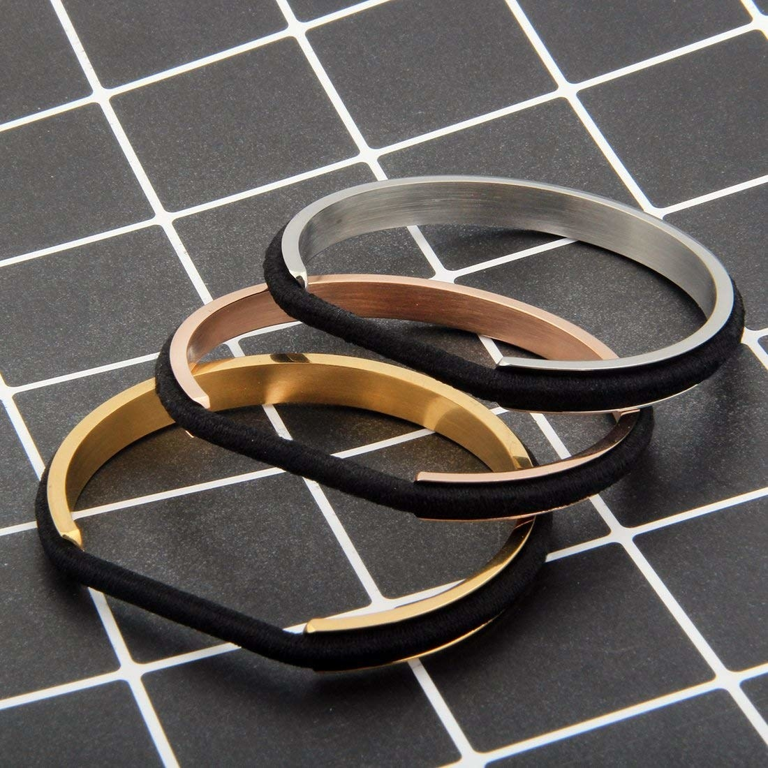 The silver rose gold and yellow gold bracelets with black hair ties around them