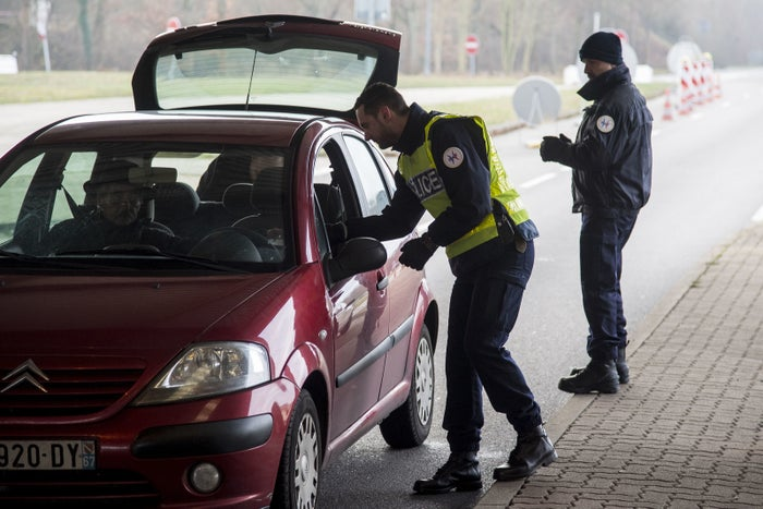 Police officers search cars at the French–German border.
