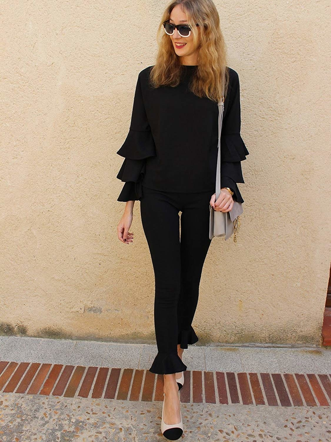 A model in the black pants with fluted ruffle around the ankle