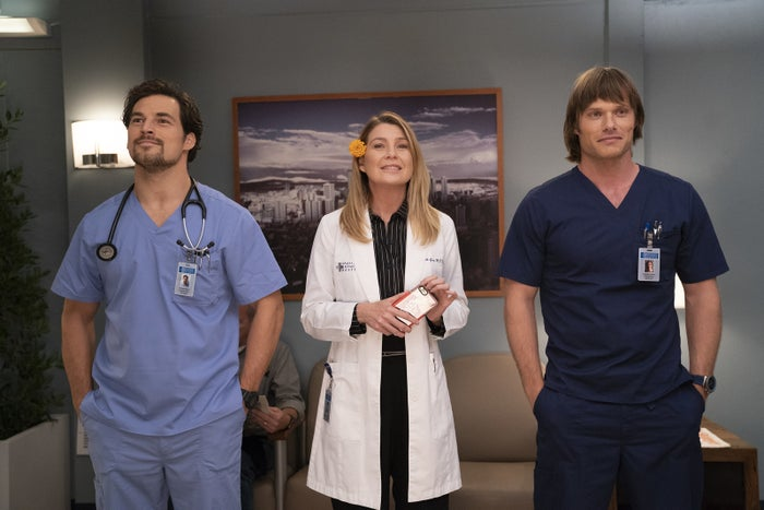 """Andrew DeLuca (Giacomo Gianniotti), Meredith Grey (Ellen Pompeo) and Atticus """"Link"""" Lincoln (Chris Carmack) wait for the elevator on Grey's Anatomy."""