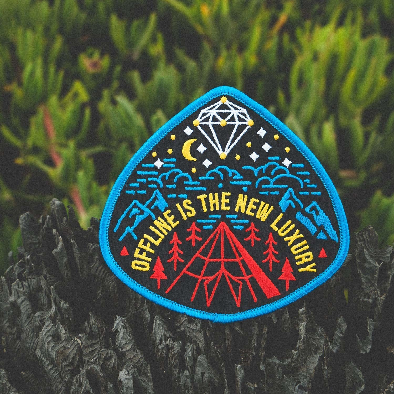"patch with mountain illustration that says ""offline is the new luxury"""