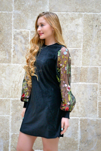 A reviewer wearing the dress in black velvet with long sheer sleeves embroidered with colorful flowers
