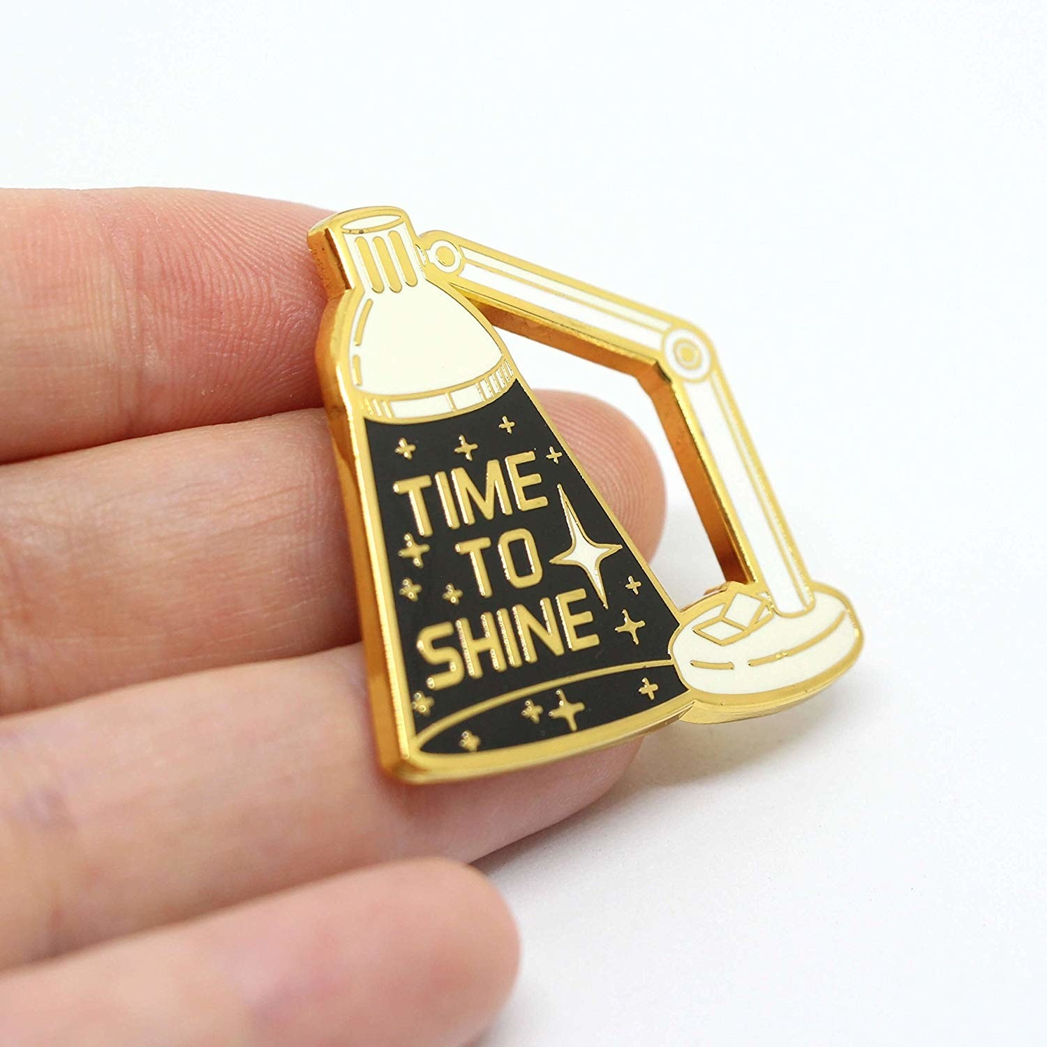 "enamel pin that looks like a desk lamp that says ""time to shine"""