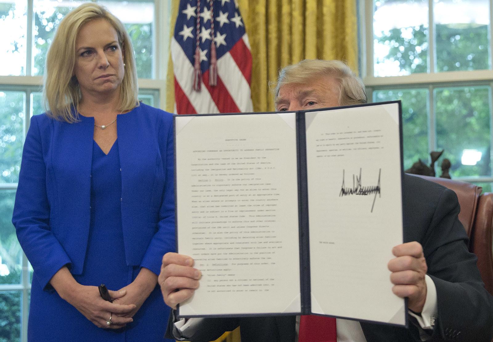 President Trump holds his executive order to end family separations, alongside Homeland Security Secretary Kirstjen Nielsen, on June 20.