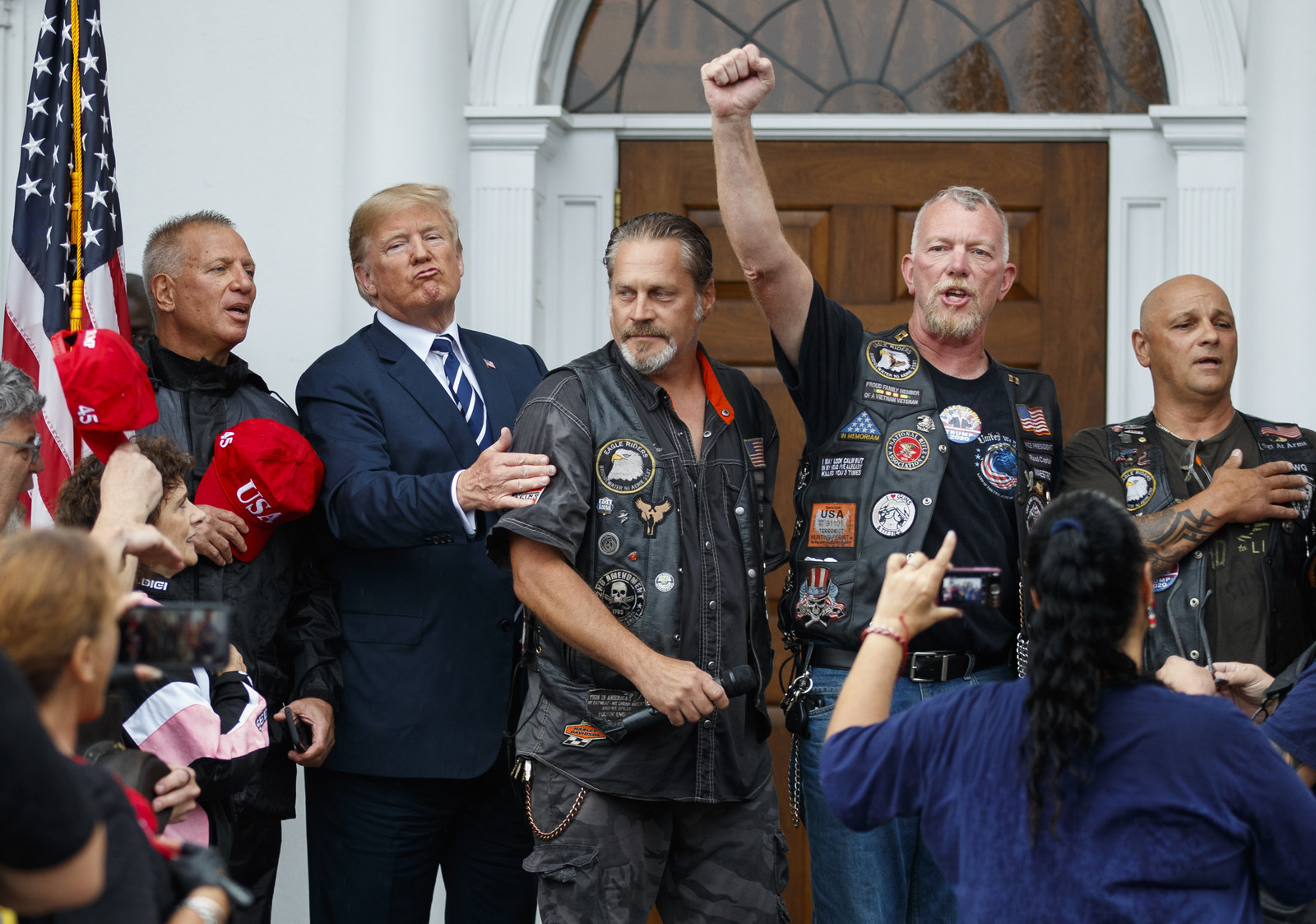 President Donald Trump stands in the rain with members of Bikers for Trump and supported after saying the Pledge of Allegiance, Saturday, Aug. 11, 2018, at the clubhouse of Trump National Golf Club in Bedminster, N.J. (AP Photo/Carolyn Kaster)