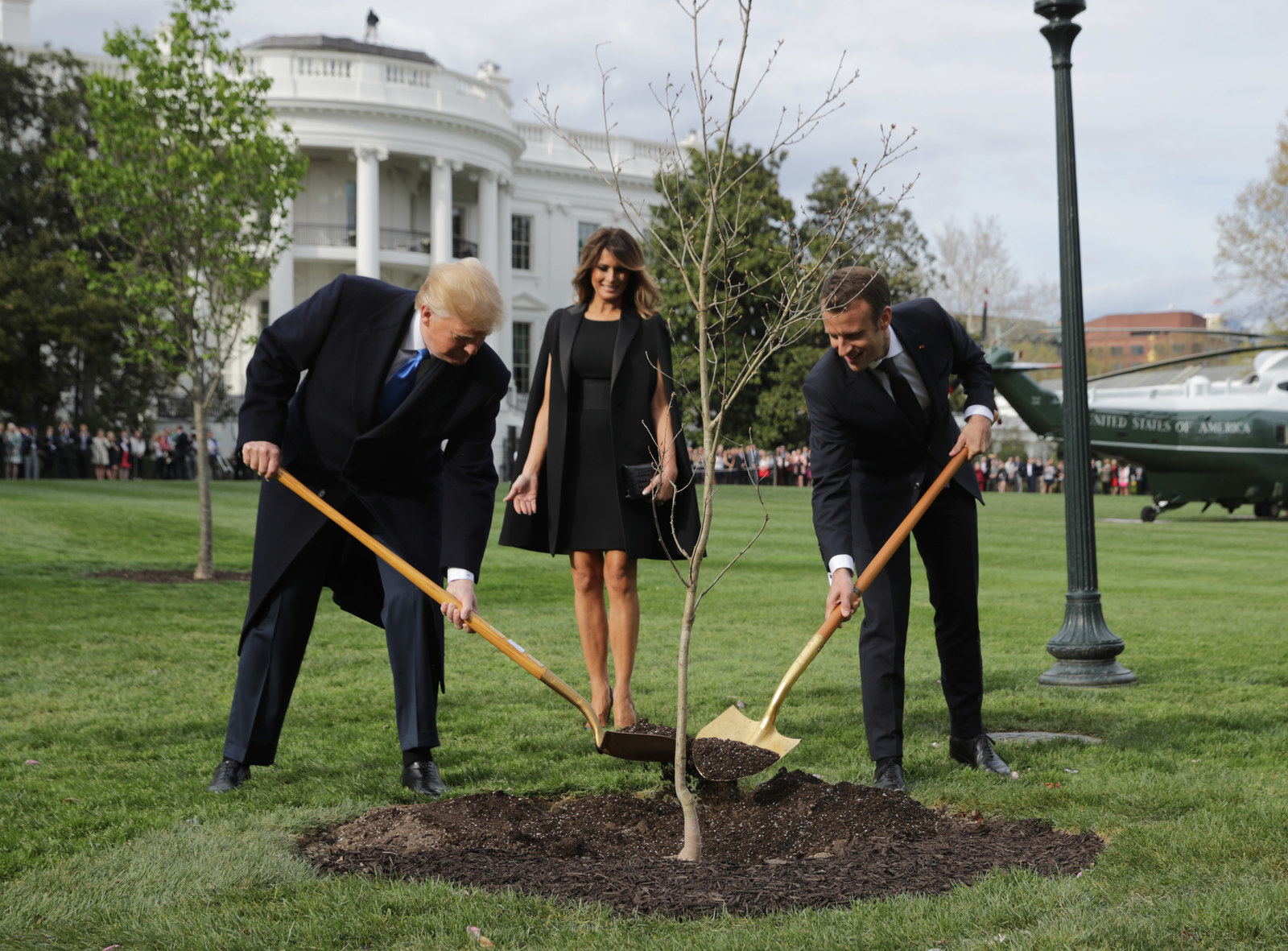 President Trump, Melania, and French President Emmanuel Macron in a tree-planting ceremony on the South Lawn of the White House on April 23.