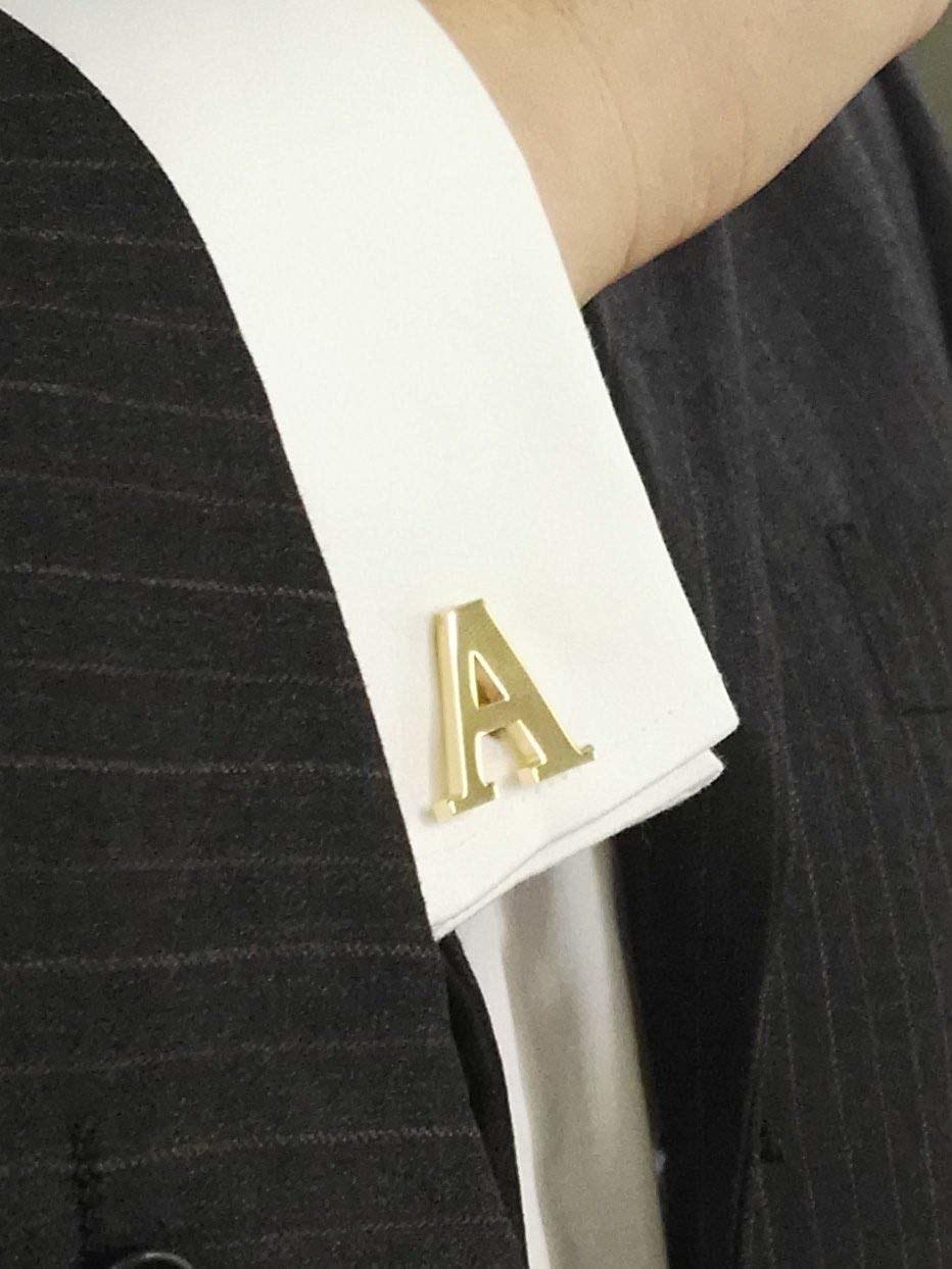 The golden letter A initial cufflinks on a shirt cuff