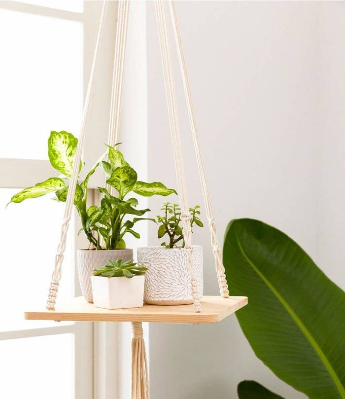 The wooden shelf hanging from white macrame and a tassel underneath
