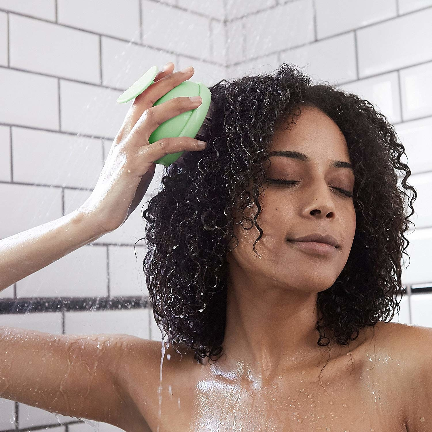 A model using the massaging tool on their scalp while washing their hair