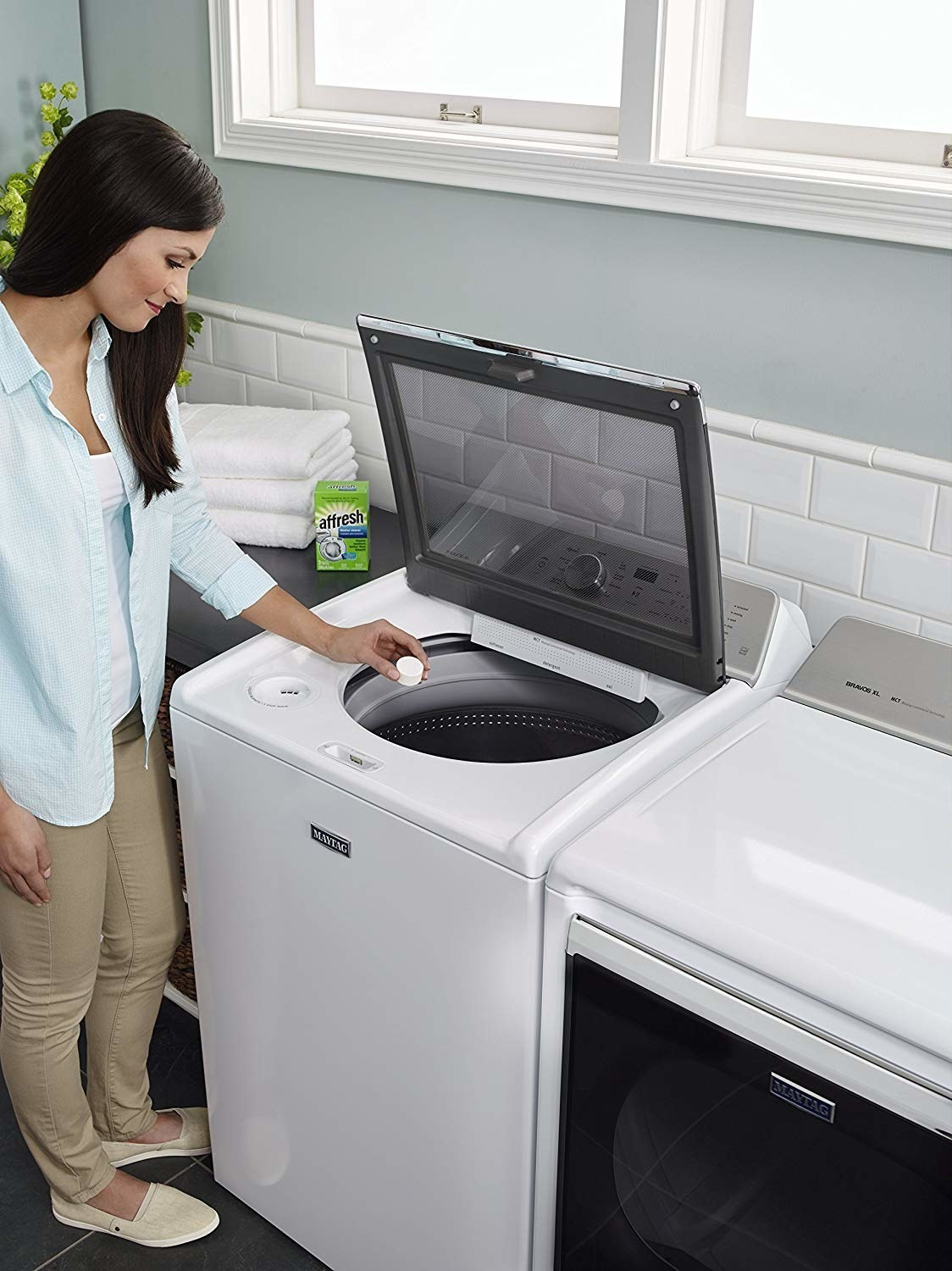 model putting a cleaning tablet into a top-load washing machine