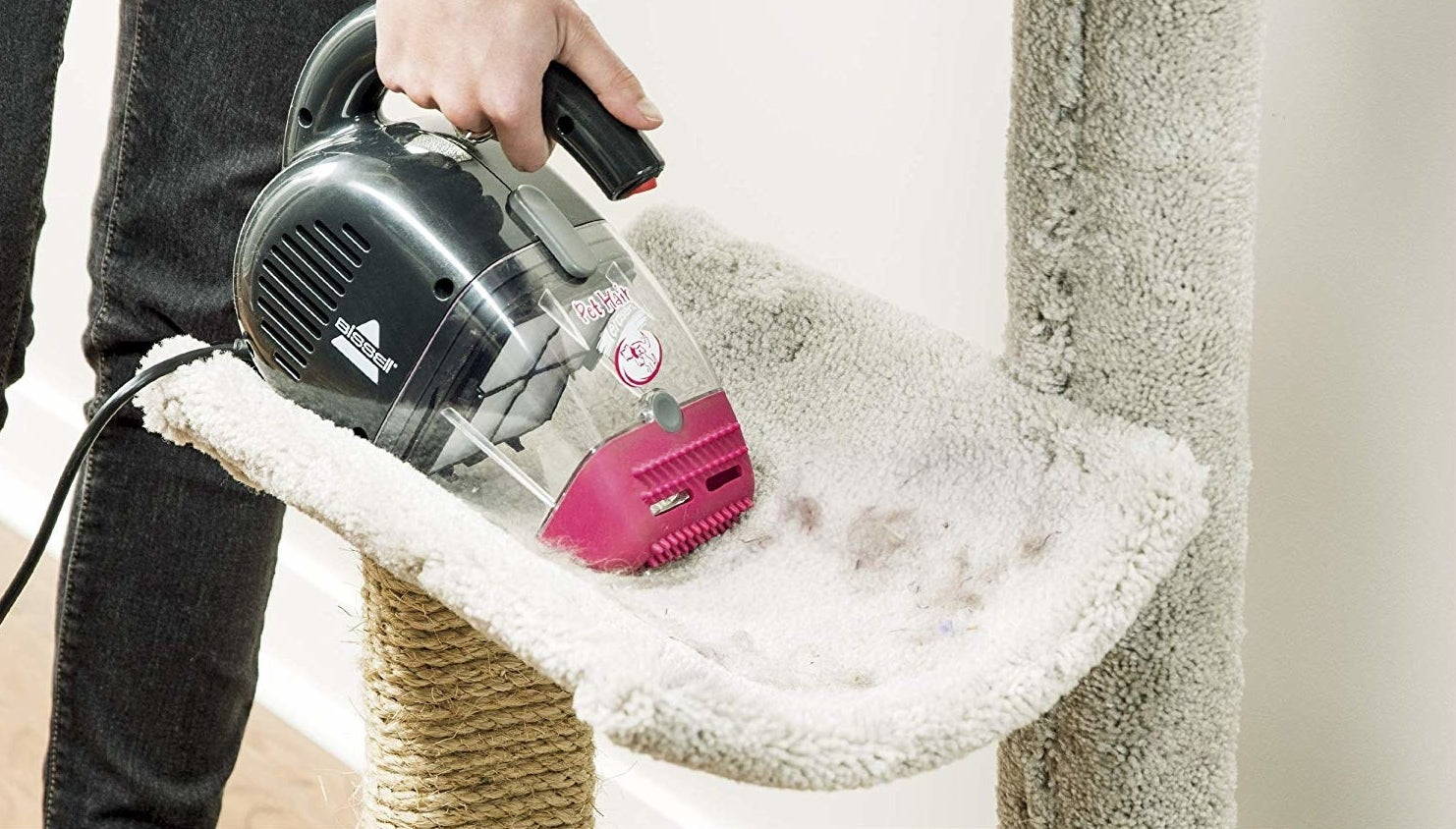 person using hand vac to suck up cat fur on a cat tree