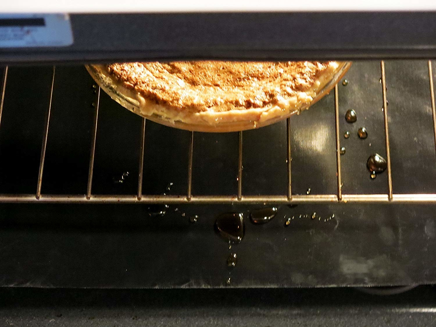 the black oven liner barely detectable in the bottom of the oven catching grease from a pizza