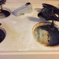 reviewer's white stovetop with tons of rusty stains