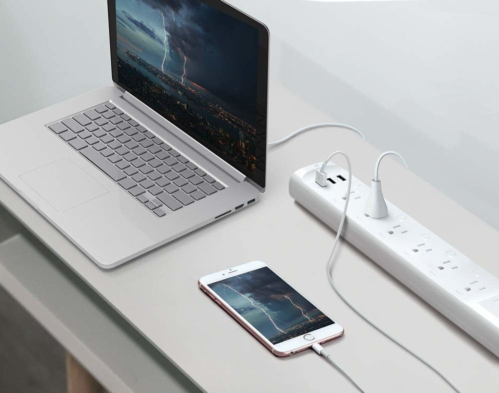 The power strip with a laptop and cell phone plugged in