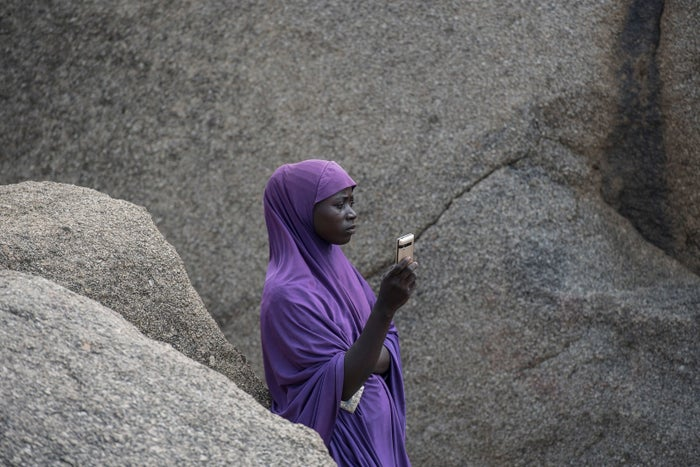 A woman waits for a call on the only hill in Pulka, Nigeria, that receives cellphone signal.