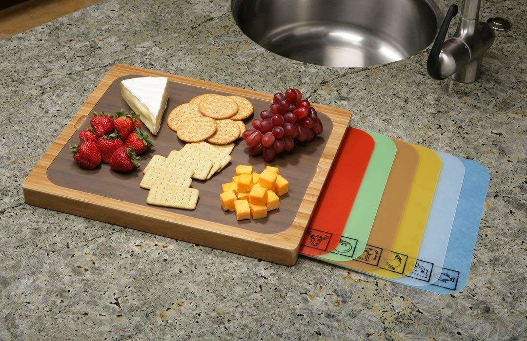 wood cutting board on kitchen counter with gray plastic mat on top of the wood and a cheese board display on top. Six similar plastic mats with icons for types of food are fanned out from beneath the cutting board
