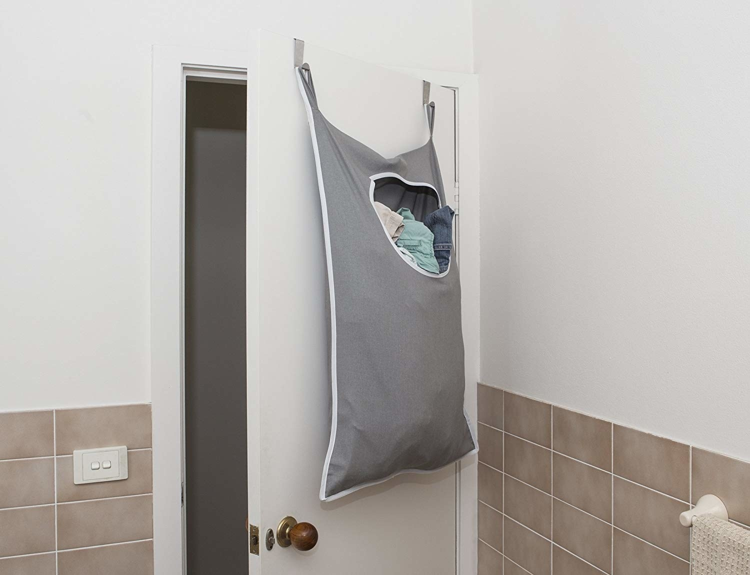 hamper bag hanging on back of bathroom door with circular opening at top for putting in the dirty clothes