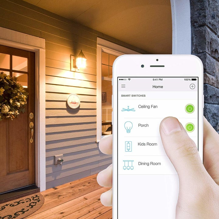 A person using the Kasa Smart Light Switch app to turn off the lights
