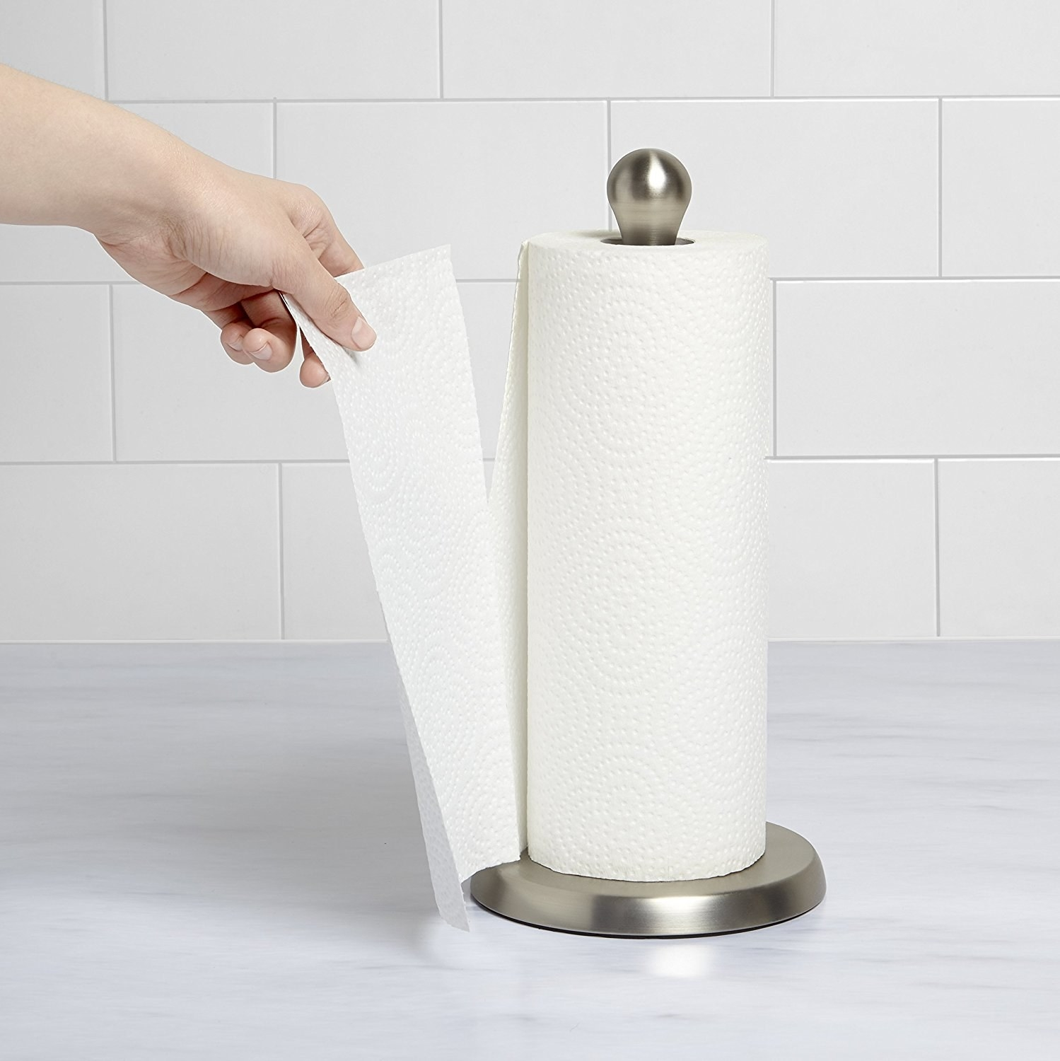 person tearing off a paper towel sheet off a paper towel holder