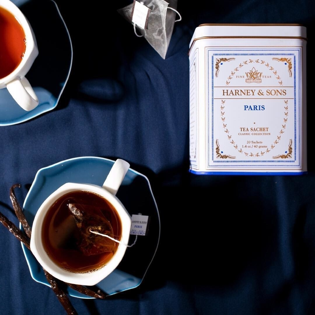 the tin of tea next to a brewed cup of tea
