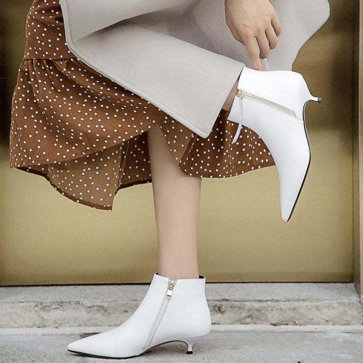 A model wearing the pointy toe booties in white