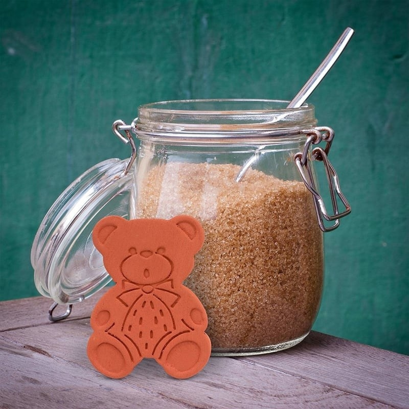 product shot of terracotta bear leaned up against an open glass canister of brown sugar