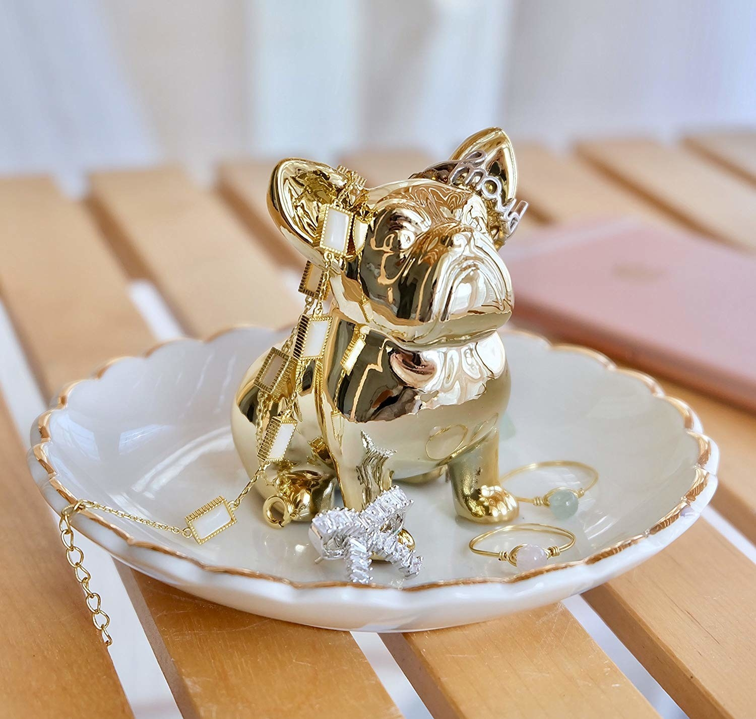 A white dish with a scalloped edge and a gold bulldog in the center with assorted rings and bracelets over it.