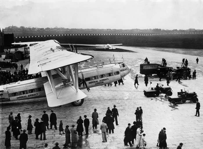Passengers wait as the Imperial Airways aircraft headed for Brisbane, Australia is towed onto the runway.