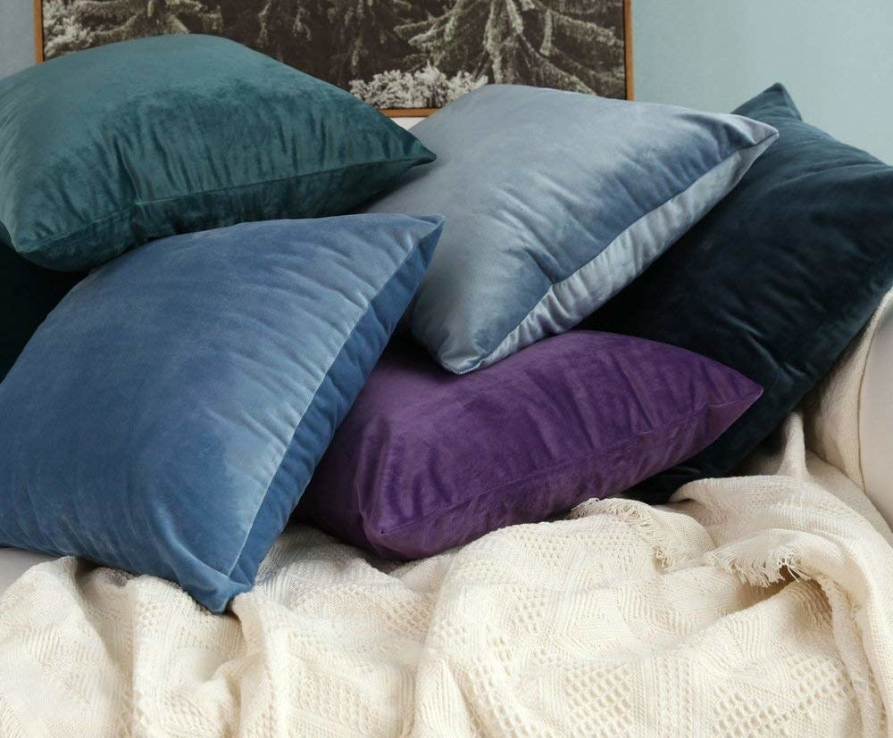 a teal, blue, light blue, purple, and navy blue velvet pillowcases on a bed