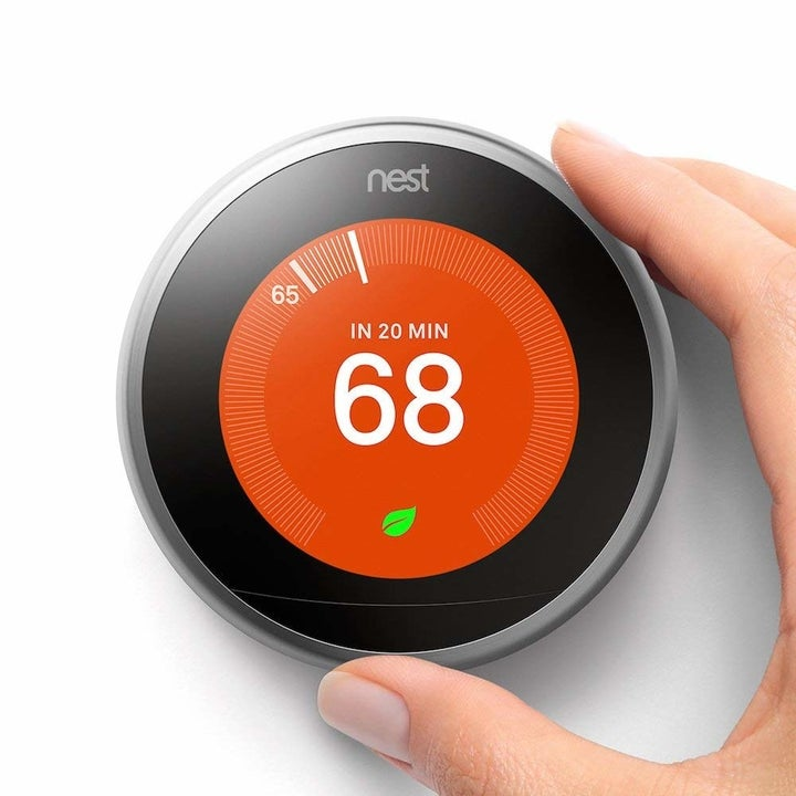 A hand adjusting the Nest thermostat