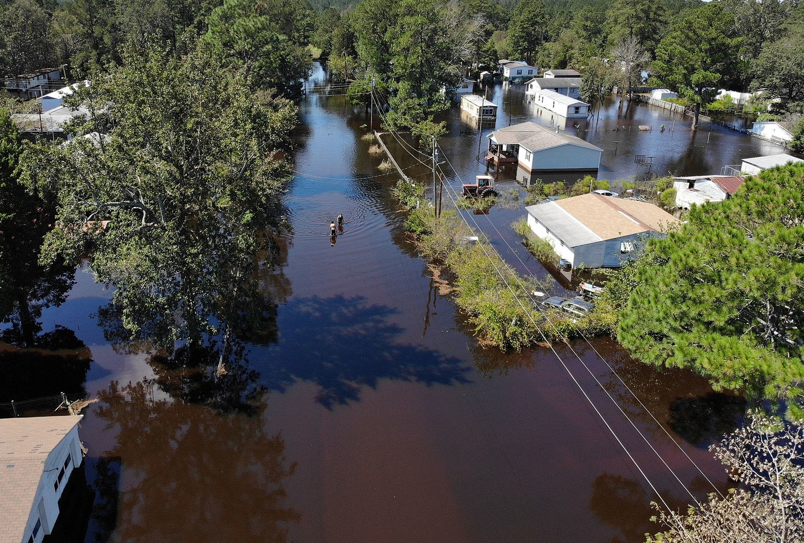 Jovani Quintano and Carlos Gomez walk through a flooded neighborhood after heavy rains brought on by Hurricane Florence, Sept. 19, in Lumberton, North Carolina.