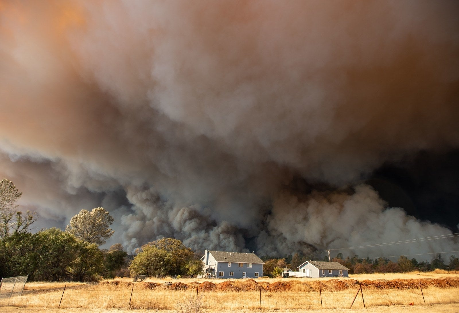 A home is overshadowed by towering smoke plumes as the Camp fire burns through Paradise on Nov. 8.