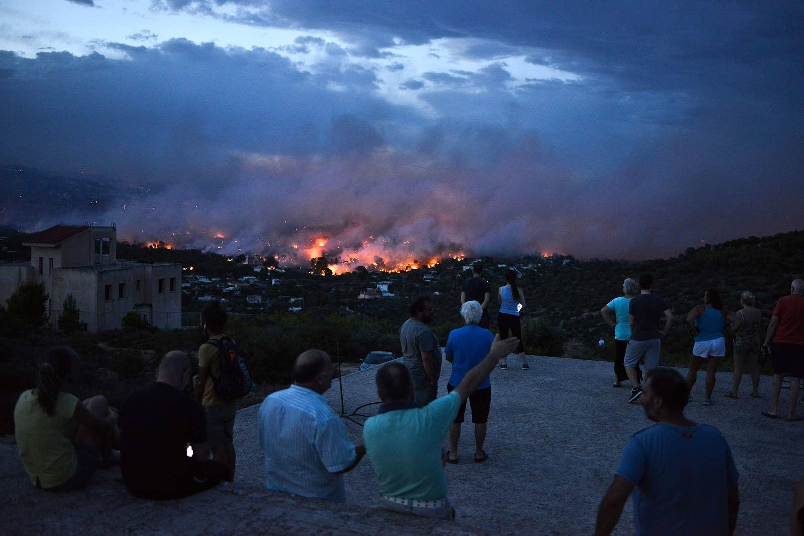 People watch a wildfire in the town of Rafina, near Athens, July 23.