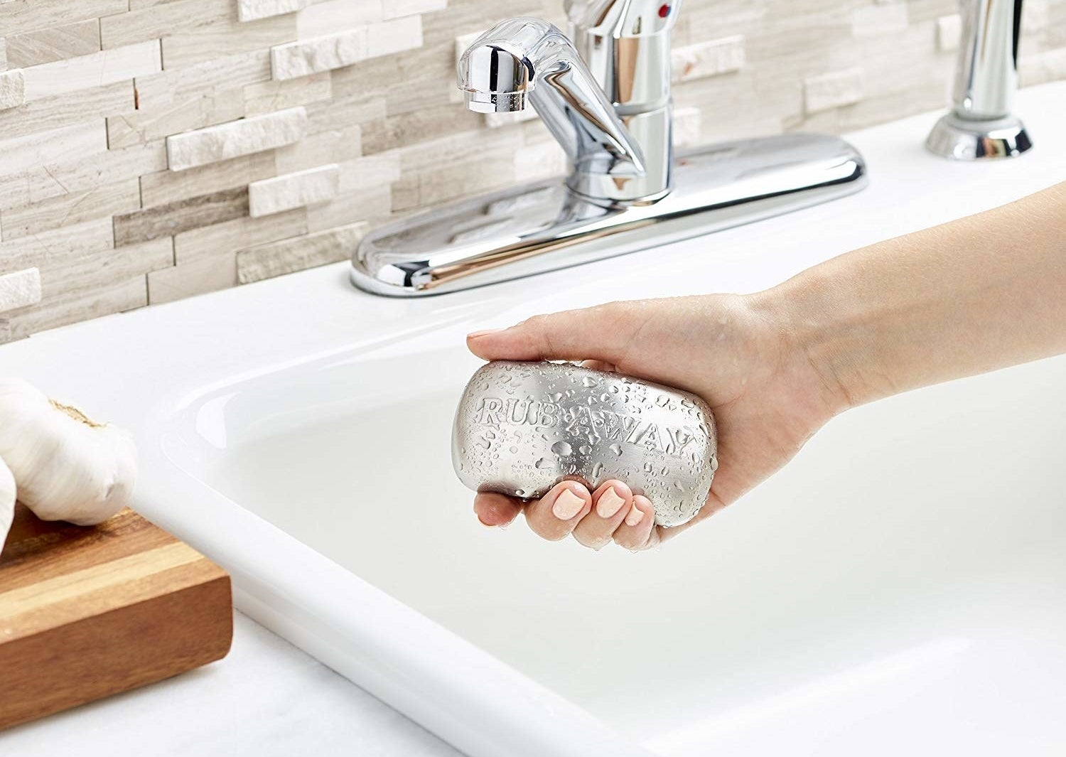 Hand holding the stainless steel in the shape of a bar of soap