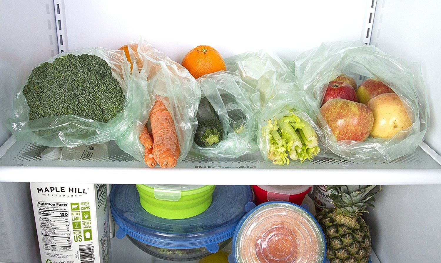A fridge shelf with produce in the green-tinted bags