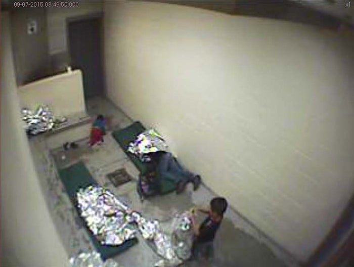 An image from an Arizona US Border Patrol surveillance video shows a child crawling on the concrete floor near the bathroom area of a holding cell, and a woman and children wrapped in Mylar sheets.