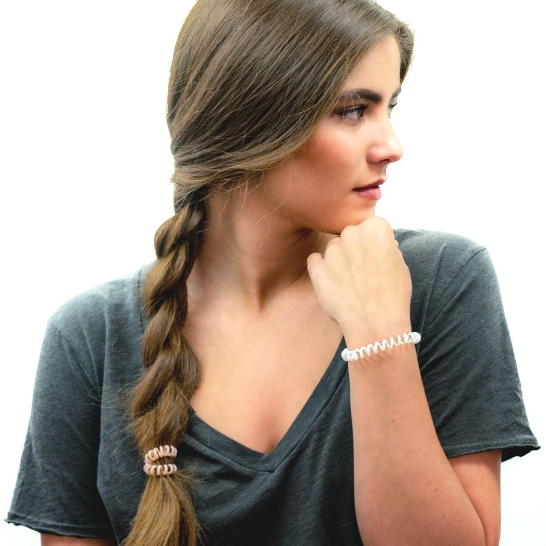A model with one cord on a braid and one on their wrist