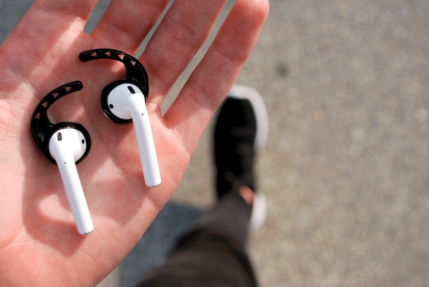 A hand with airpods in them, with the hook-like black silicone attachments