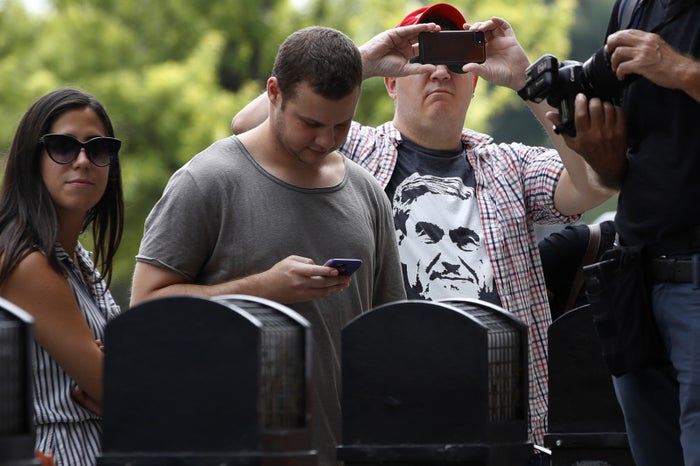 A man takes a photo of the media as he wears a T-shirt of special counsel Robert Mueller, at a federal court for sentencing, Sept. 7 in Washington.