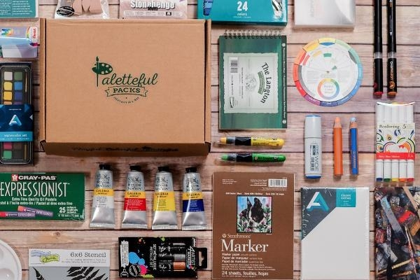 paints, markers, oil pastels, sketchbooks, and other art supplies next to a subscription box