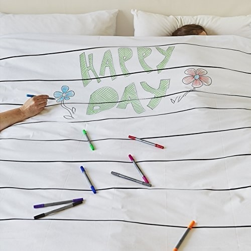 person writing on a comforter with markers